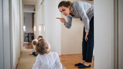 Mutter beugt sich zu Tochter runter und schüttelt den Zeigefinger