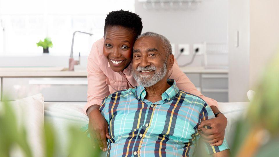 Ein Mann und eine Frau lachen Arm in Arm in die Kamera