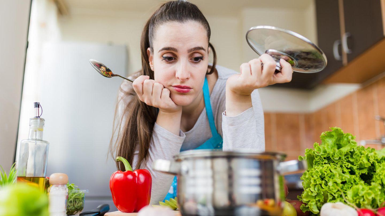 Frau schaut enttäuscht in den Koch