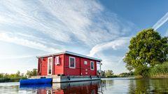 Ein rotes Hausboot schwimmt auf einem See in Brandenburg