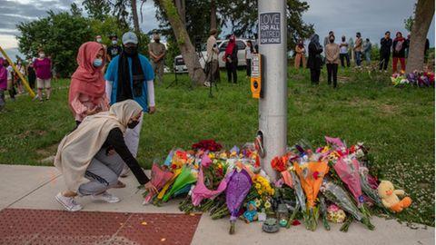 Frauen mit Hijab trauern um die Opfer eines mutmaßlich antimuslimischen Angriffs und legen Blumen an einer Ampel nieder