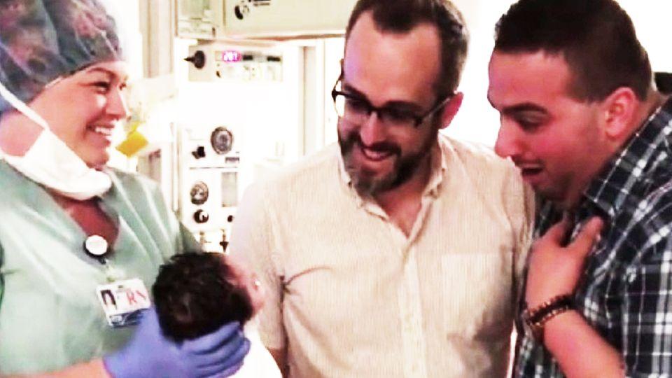 Schwules Paar sieht zum ersten Mal neugeborene Tochter