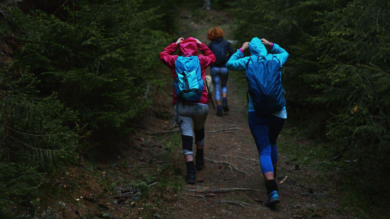 Wasserdichter Rucksack: Drei Wanderer mit Rucksäcken bei Regenwetter