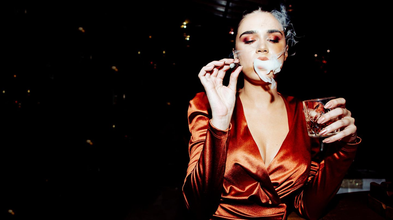 Frau in Partykleid hält Drink in der Hand und raucht