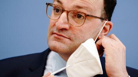 Ein weißer Mann mit braunen Locken und dünner Hornbrille nimmt eine FFP2-Maske ab, die mit einem Gummi noch am linken Ohr hängt