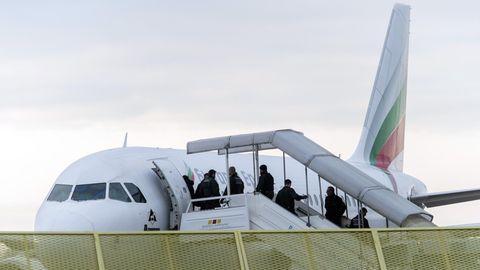 Hinter einem grünen Drahtzaun ist zu sehen, wie Menschen über eine überdachte Gangway ein Flugzeug besteigen