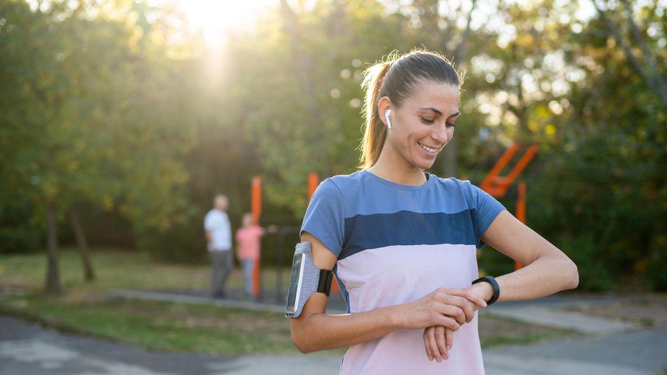 Eine Läuferin schaut auf ihre Fitness-Uhr