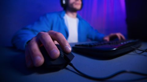 MMO-Maus: Ein Mann spielt am Computer. Mit seiner rechten Hand steuert er die Maus.