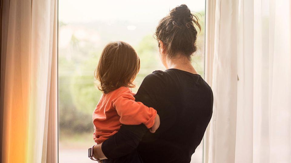 Frau trägt Kleinkind auf dem Arm und schaut aus dem Fenster