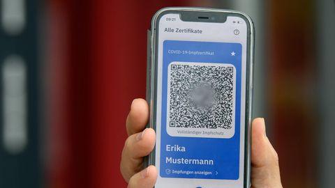 Eine rechte Hand hält ein Smartphone hoch, auf dem ein QR-Code mit blauem Rahmen aufleuchtet