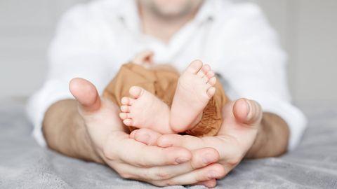 Die kleinen Füße eines kleinwüchsigen Babys in den Händen eines Erwachsenen