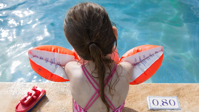 Ein kleine Mädchen sitzt mit Schwimmflügeln am Beckenrand