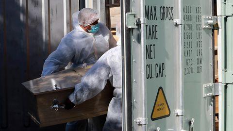 Corona-Pandemie: Bestattungsarbeiter inKapstadt, Südafrika lagern einen Sarg in einem Kühlcontainer