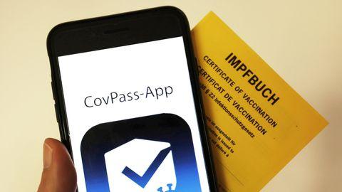 """Eine Hand hält einen gelben Impfpass und ein Smartphone mit der """"CovPass-App"""" auf dem Display hoch"""