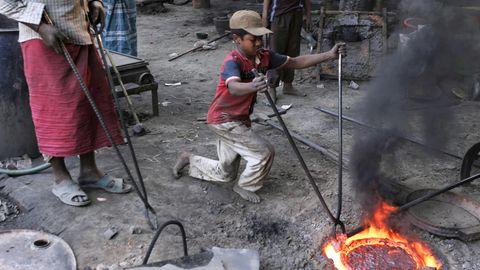 Mit einer langen Zanke hält ein Junge in schmutziger Kleidung eine Gussform, in der Metall glüht