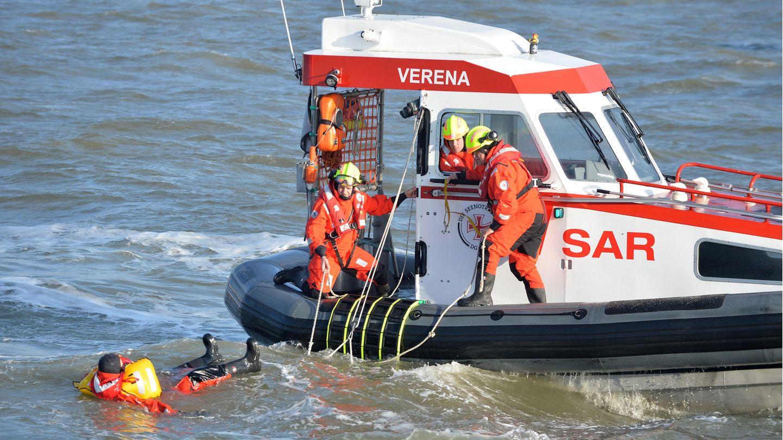 Zwei Personen in rot-schwarzen Overalls und gelben Helmen stehen am Rand eines Boots und schauen auf einen im Wasser treibenden