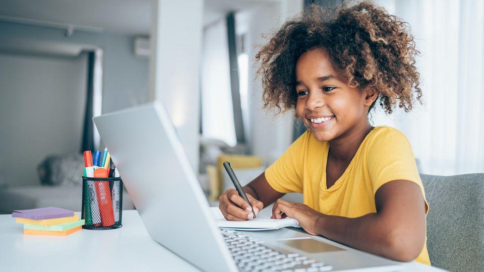 Mädchen sitzt vor ihrem Laptop und schreibt sich Sachen auf einen Collegeblock