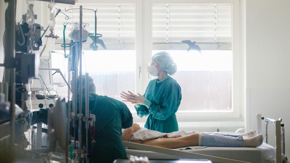 Intensivpflegerinnen versorgen einen Patienten
