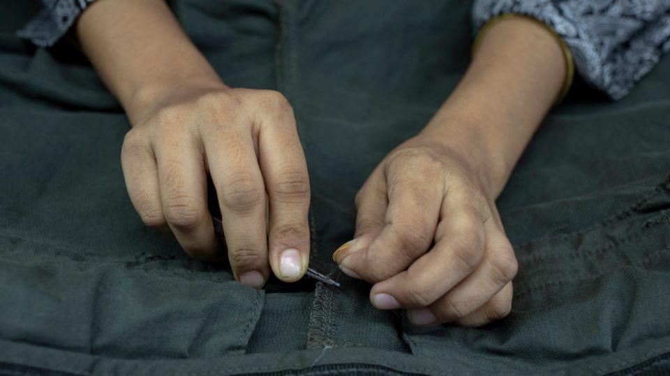 Kinderhände nähen eine Jacke zusammen.