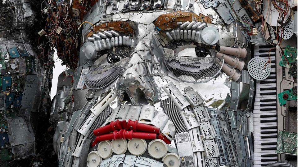 Aus Keyboards, Platinen und anderem Müll haben Protestierende den Kopf von Merkel überlebensgroß nachgebildet