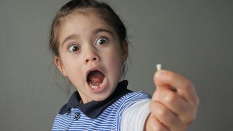 Kleines Mädchen reißt erstaunt den Mund auf und schaut auf den Zahn, den sie in der Hand hält