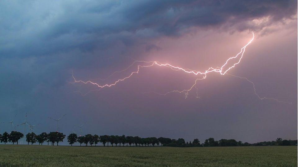 Ein Blitz erhellt den Abendhimmel über der Landschaft im Landkreis Oder-Spree. Wie ein Gewitter entsteht, erfahren Sie unten.