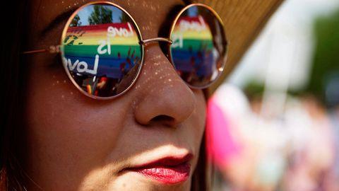 Eine Frau trägt eine Sonnenbrille, in der sich Regenbogenfarben spiegeln