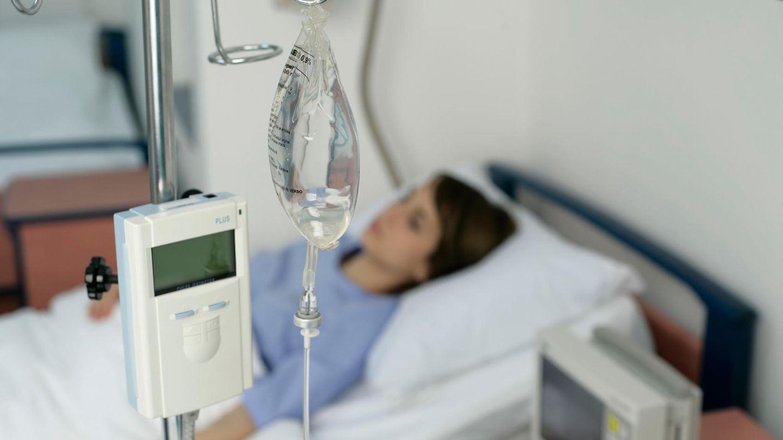 Eine Frau liegt am Tropf in einem Krankenhausbett