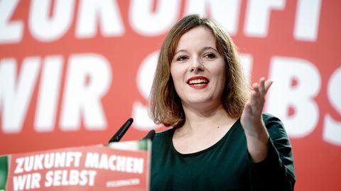 """Eine junge Frau mit schulterlangen Haaren hält eine Rede vor einer roten Wand mit weißer Schrift """"Zukunft machen wir selbst"""""""