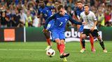 Antoine Griezmann bläst die Wangen zusammen während er den Ball schießt