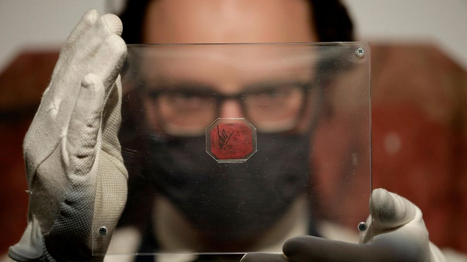 Ein weißer Mann hält sich mit weißen Handschuhen eine Plexiglasscheibe mit einer magenta-farbenen Briefmarke vors Gesicht