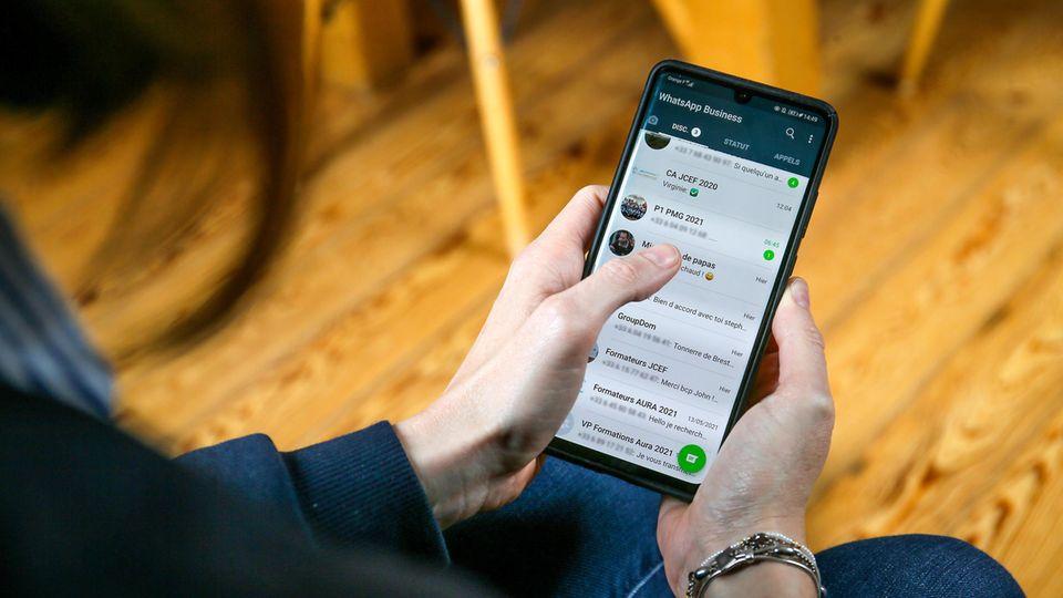 Eine Perosn blickt auf ihre geöffnete Chat-Liste bei WhatsApp