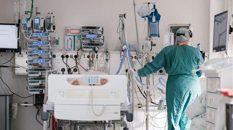 Eine Intensivpflegerin versorgt auf der Intensivstation am Klinikum Braunschweig einen an Covid-19 erkrankten Patienten