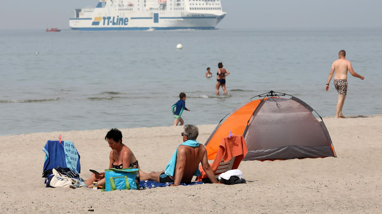 Menschen genießen den Ostseestrand, im Hintergrund ein Schiff der TT-Linie