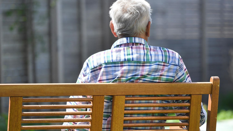 Ein älterer Mann sitzt auf einer Bank