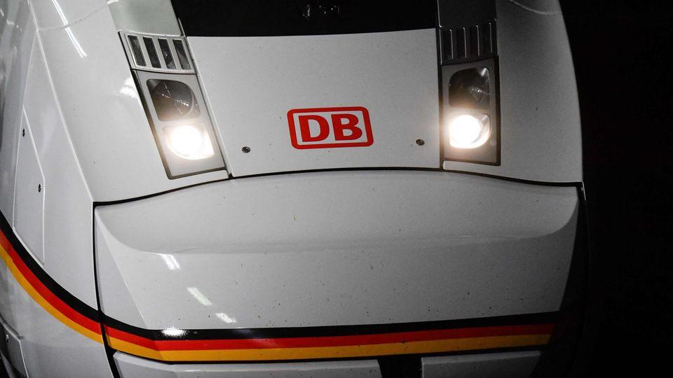 """Die weiße Lok eines ICE 4 steht mit rotem """"DB""""-Logo zwischen den angeschalteten Scheinwerfern in einem Bahnhof"""