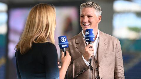 Jessy Welmer, ARD-Moderatorin, und Bastian Schweinsteiger, TV-Experte der ARD, stehen im Stadion.