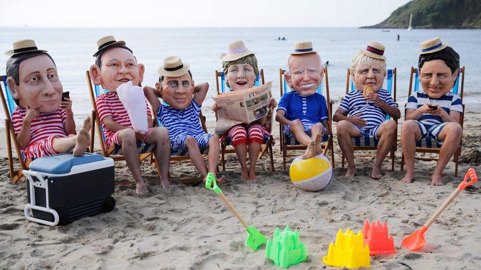 St Ives, Vereinigtes Königreich: Mit Pappmaché-Köpfenals Staats- und Regierungschefs verkleidete Aktivisten der Nichtregierungsorganisation Oxfam fodern am Rande des G7-Treffens, Emissionen schneller und stärker zu senken und mehr Geld für ärmere Länder bereitzustellen,auf die Auswirkungen des Klimawandels zu reagieren.