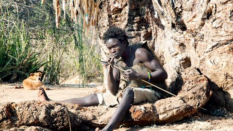 Ein junger Mann vom Volk der Hadza fertigt einen Bogen