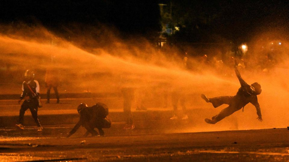 Bogotá, Kolumbien. Die – teils gewaltsamen – Proteste in dem südamerikanischen Land gegen die Regierung lassen sich nicht zu Fall bringen, im Gegensatz zu diesem Demonstranten, der von einem Wasserwerfer der Polizei getroffen wird.