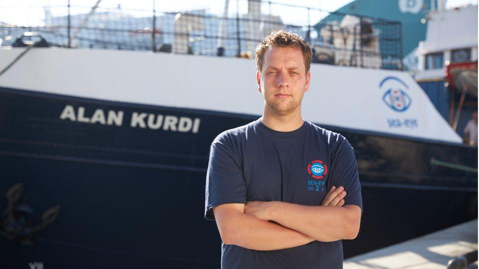 Ein Mann steht mit verschränkten Armen vor einem Schiff mit dem Namen Alan Kurdi