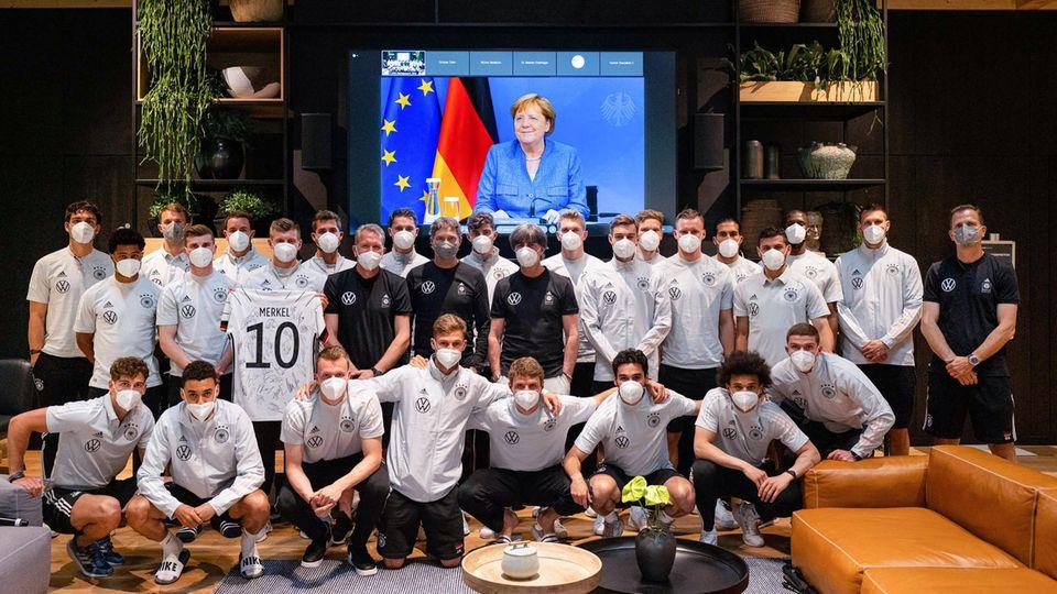 Toni Kroos hält ein Trikot mit dem Nachnamen von Kanzlerin Merkel hoch, er und das restliche Team posieren für ein Foto