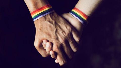 Zwei Männer mit regenbogenfarbigen Armbändern halten Händchen