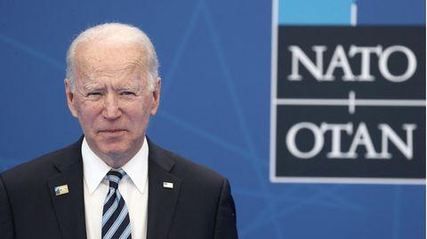 Ein weißer weißhaariger Mann in Anzug und Krawatte steht vor einer blauen Wand mit schwarz-weißem Nato-Schriftzug