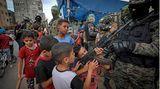 Gaza-Stadt, Gazastreifen. Eine Gruppe von Kindern hat sich um Mitglieder der Kassam-Brigaden versammelt und begutachtet das Schnellfeuergewehr eines der Kämpfer. Die Kassam-Brigaden sind eine militärische Unterorganisation der palästinensischen, militanten Hamas. Die Europäische Union führt sie auf ihrer Liste der Terrororganisationen.