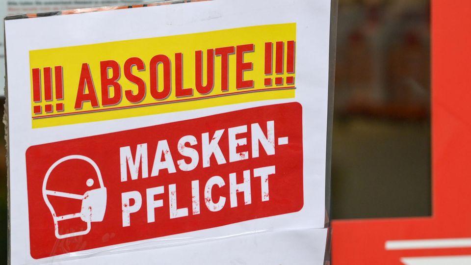 """""""Absolute Maskenpflicht"""" steht auf einem Schild am Eingang eines Geschäfts"""