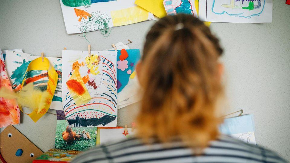 Christina S. in ihrer Wohnung, vor Bildern, die ihre Kinder gemalt haben