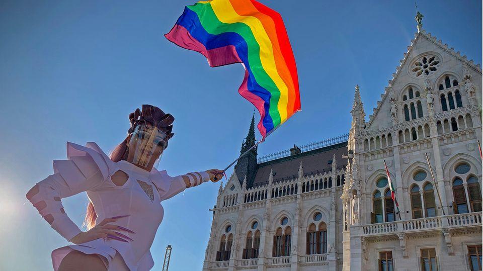 Eine Drag Queen schwenkt eine Regenbogenfahne auf einer LGBT-Rechte-Demonstration vor dem ungarischen Parlament