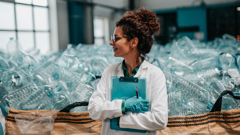 Frau in einem Kittel steht vor riesigen Säcken mit Plastikflaschen