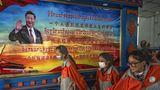 Die Journalistengruppe wird unter anderem durch eine tibetische Schule geführt. Zu den Schülern winkt zweisprachig Chinas Präsident Xi Jinping von der Wand.